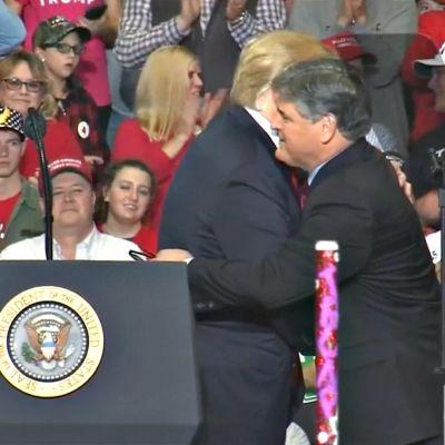 Presidentti Donald  Trump ja Sean Hannity halaavat lavalla.