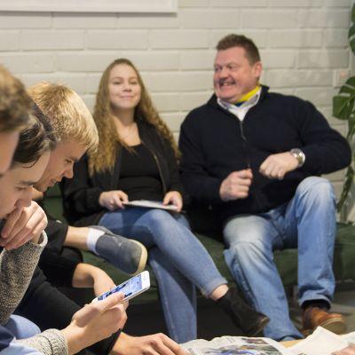 Nuoret istuvat opettajan seurassa sohvalla koulun käytävällä.
