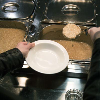 Puuroa otetaan jakolinjastolta lautaselle.