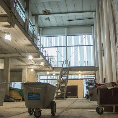 Mies katsoo rakenteilla olevan sairaalan uutta sisäänkäyntiä.
