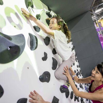 Nuori tyttö kiipeilyseinällä, häntä tukee nuori nainen alapuolelta.
