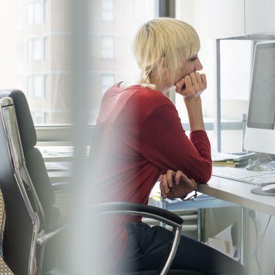 Nainen istuu toimistossa tietokoneen äärellä.