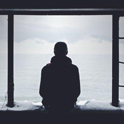 Mies istuu ikkunalaudalla ja katsoo kauas synkkänä