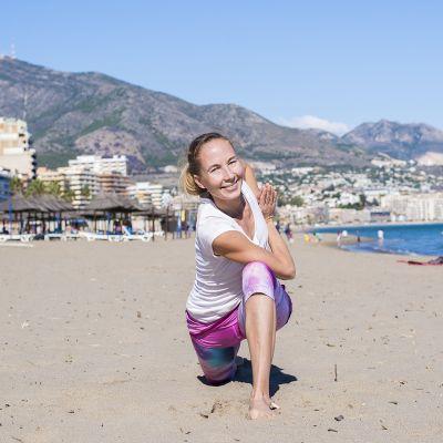 Nainen joogaa rannalla.