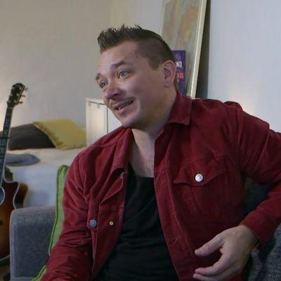 En artist hemma i sitt vardagsrum, en gitarr bakom.