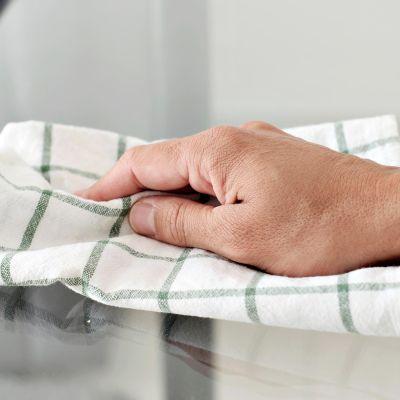 Käsi pyyhkii liinalla pintoja puhtaaksi.