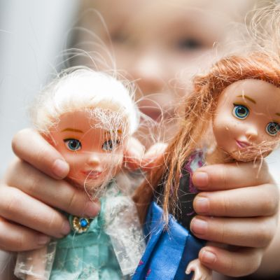 Tyttö pitää Frozen-nukkeja kädessä.