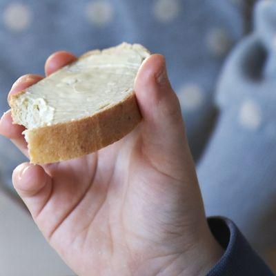 Lapsen kädessä voileipä.