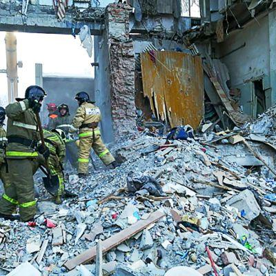Pelastustyöntekijöitä romahtaneen talon raunioissa.