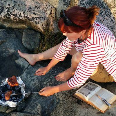 Nainen paistaa makkaraa kalliolla.
