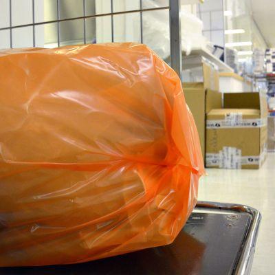 Oranssi muovinen jätesäkki rullakossa sairaalan käytävällä.