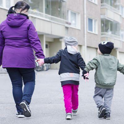 En mamma går hand i hand med två barn