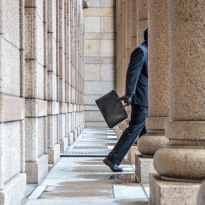 Henkilö kävelee ulos eduskunnasta.