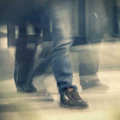 Nuori ihminen kävelee farkut ja kengät jalassaan.