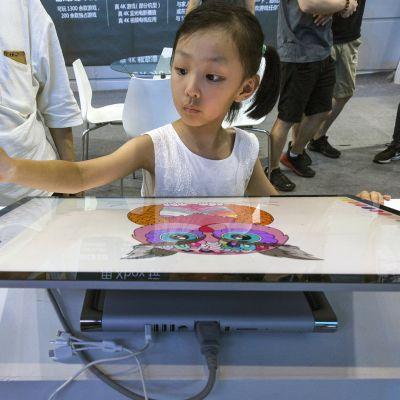 Tyttö kokeilee isoa piirtopöytää.