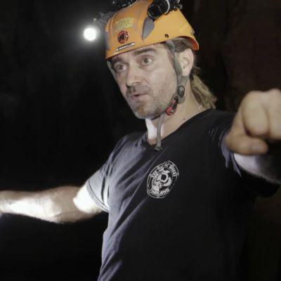 Mikko muistelee tapahtumia kädet levällään pimeässä luolassa otsalampun valossa.