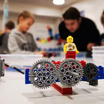 Legoista rakennettu kone ja takana ihmisiä.