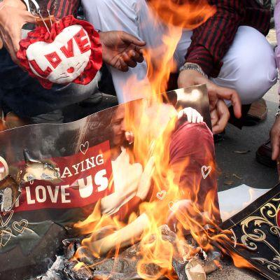 Miehet polttavat nuotiolla rakkauden symboliikkaa edustavia sydämiä ja julisteita.