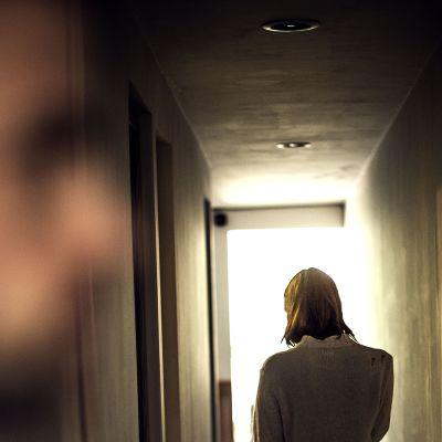 Etualalla epäselvä mies hahmo ja käytävällä edempänä nainen.