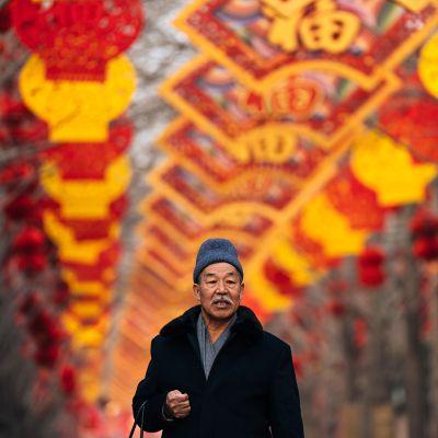 Kiinalainen mies kävelee punakeltaisten lyhtyjen alla jotka on ripustettu uuden vuoden juhlintaa varten.