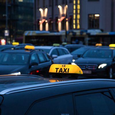 Taksinkuljettavat odottavat asikkaita taksitolpalla.