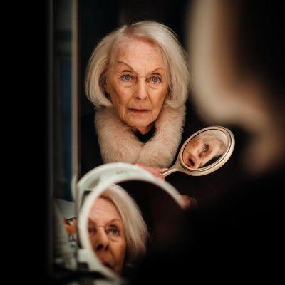 Näyttelijä Seela Sella istuu peilin ääressä ja katselee itseään. Hänen kasvonsa heijastuvat myös kädessä olevasta peilistä.