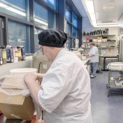 Ulla Leinonen tekee Runebergin torttujen taikinaa, ja taustalla Taina Mustanoja leipoo viinereitä.