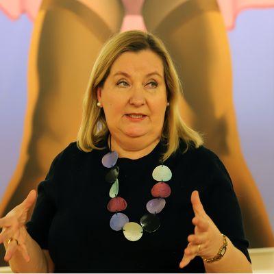 Museonjohtaja Katriina Pietilä-Juntura taustallaan Esko Tirrosen maalaus Striptease Aineen kuvataidesäätiön kokoelmista.