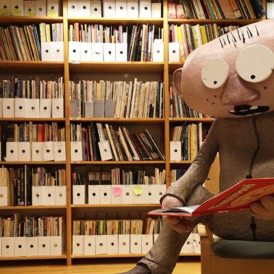 Sarjakuvasta tuttu Heimo Vesa -hahmo lukee sarjakuvaa, taustalla osa Kemin sarjakuvakeskuksen sarjakuvakokoelmasta.