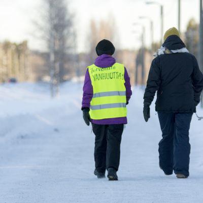 """Kaksi naista kävelee talvisella kävelytiellä. Toisen huomioliivin selässä on teksti """"Turvallista vanhuutta""""."""