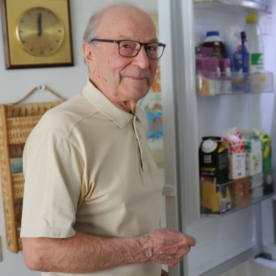 Lauri Laine avaa jääkaapin oven.