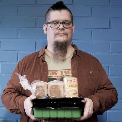 Markku Korhonen pitää ruokajakelusta saatuja ruokia käsissään.