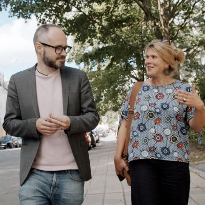 en man och en kvinna som går på gatan och pratar med varandra