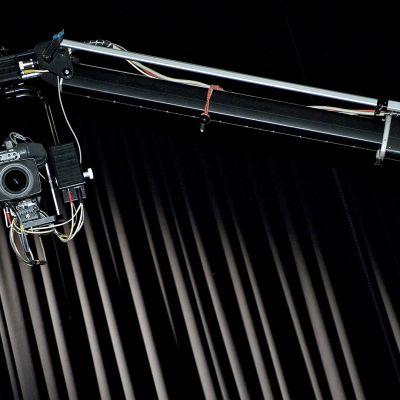 Kraana ja videokamera studiossa esiripun edessä.