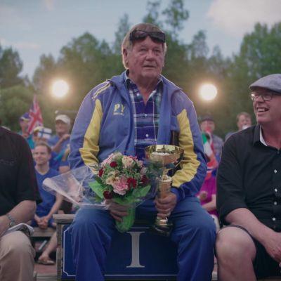 Kolme varttunutta miestä istuvat urheilukentällä palkintopallilla yleisön hurratessa takana. Miehet katsovat eteenpäin, kohti showta, joka ei näy kuvassa.