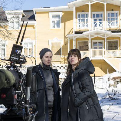 Näyttelijät Sofia Pekkari ja Pihla Viitala televisiosarjan kuvauksissa vanhan kartanon lumisella pihalla.