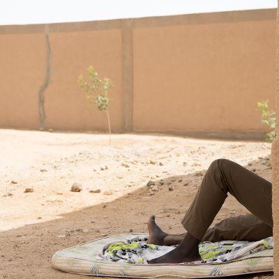 Pakolainen lepää leirillä Agadezissa, Nigerissä.