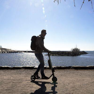 Mies vauhdissa sähköpotkulaudalla lämmittävässä kevätauringossa Helsingin Merisatamassa