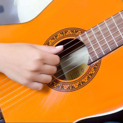 Tyttö soittaa kitaraa.