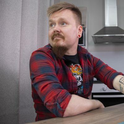 Petri Vuomajoki istuu keittiönpöydän ääressä.