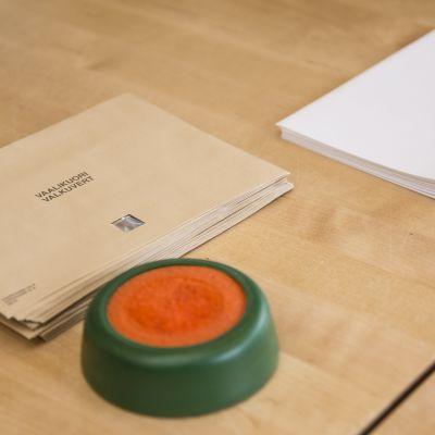 Vaalikuoria ja äänestyslippuja pöydällä.