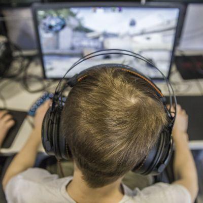 Lapsi pelaa peliä tietokoneella kuullokkeet päässään