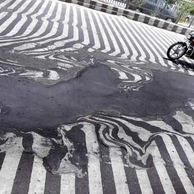 Mopedisti ajaa tiellä jossa osa valkoisesta viivoituksesta on sulanut kuumassa auringossa.