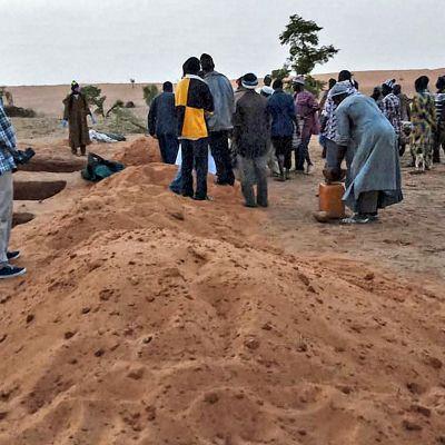 Dogon-heimon jäsenet sekä viranomaiset seisovat lähellä hautoja Sobane Dan kylässä Malissa 11. kesäkuuta.