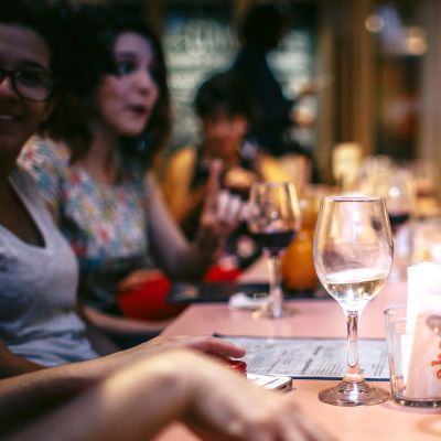 En grupp människor som sitter vid ett matbord med vinglas i handen.