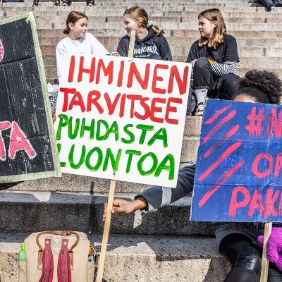 Nuoret osoittavat mieltään Tuomiokirkon portailla.