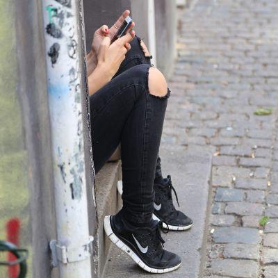 Teini käyttää kännykkää.