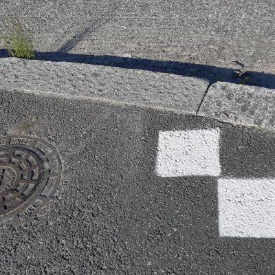Asfalttiin on maalattu kaksi pientä valkoista neliötä.
