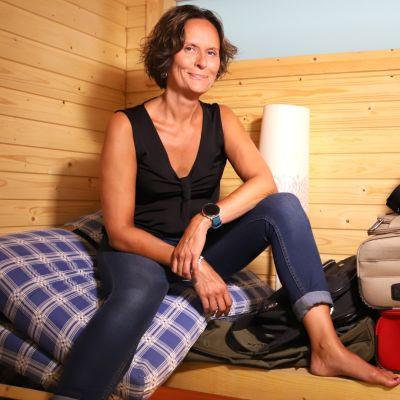 Nainen istuu saunassa, joka on täynnä rojua.