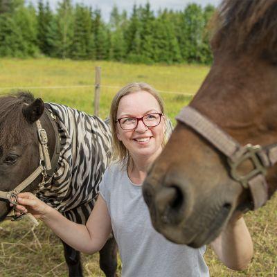 Sini Liukkonen on kyykyssä kahden ponin välissä ja pitää poneja päitsistä.